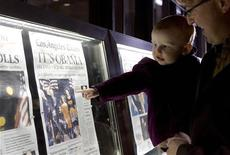 <p>Nora Sherman, 18 months old, and her father Paul Sherman of Washington view the front pages of Wednesday's newspapers from around the world on display outside the Newseum in Washington, November 5, 2008. REUTERS/Molly Riley</p>