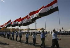 <p>Policemen hold Iraqi national flags as they march during a graduation ceremony in Tikrit, 150 km (95 miles) north of Baghdad, November 8, 2008. REUTERS/Sabah al-Bazee</p>