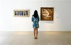 "<p>A woman stands between Francis Bacon's ""Three Studies for a Self Portrait"" (L) and Lucian Freud's ""Naked Portrait with Reflection"" at Christie's auction house in London May 19, 2008. REUTERS/Luke MacGregor</p>"