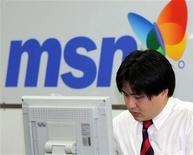 <p>Un uomo lavora al computer. Alle sue spalle un cartellone pubblicitario del servizio di instant messaging di Microsoft. REUTERS/You Sung-Ho</p>