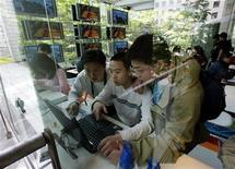<p>Japanese boys surf the net in the Nakata.net cafe in Tokyo, April 19, 2002. . REUTERS/Ruben Sprich</p>