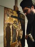 """<p>Un monje ortodóxo griego reza en frente al cuadro """"Jesús desciende de la cruz"""", el cual fue repatriado a Grecia, 19 nov.Gran Bretaña devolvió el miércoles un ícono del Imperio Bizantino del siglo XIV a autoridades griegas, 30 años después de que fuera robado de un monasterio en el norte de Grecia, dijo el ministerio de Cultura. REUTERS/Yiorgos Karahalis</p>"""
