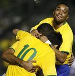 <p>Brasileiros comemoram gol de Luis Fabiano (entre Robinho e Kaká) contra Portugal. REUTERS/Jamil Bittar (BRAZIL)</p>