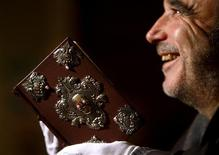<p>Barry Cunningham holds his one of only seven copies of JK Rowling's 'The Tales of Beedle the Bard' book during a press preview at the National Library of Scotland in Edinburgh, Scotland, December 3, 2008. REUTERS/David Moir</p>