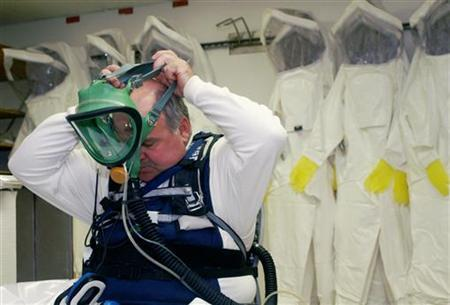Worker Rod Holum puts on fully sealed protective garments prior to entering a highly toxic area, at the Deseret Chemical Depot in Utah August 22, 2006. REUTERS/Adam Tanner