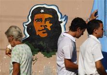 "<p>People stand next an image of late rebel leader Ernesto ""Che"" Guevara in Cardenas, December 6, 2008. REUTERS/Claudia Daut</p>"