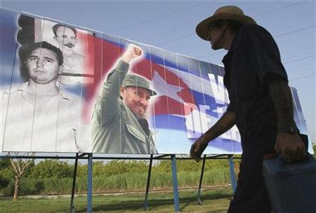 A man walks past a billboard with pictures of retired Cuban leader Fidel Castro in Havana August 12, 2008. REUTERS/Stringer