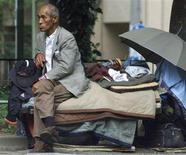 <p>A homeless man sits on blankets piled up with his belongings on a park bench in Tokyo in a file photo. REUTERS/Eriko Sugita</p>