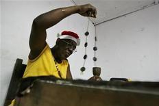 <p>Foto de archivo de un sacerdote babalawo durante una atención a un cliente en La Habana, 4 mayo 2007. Un grupo de sacerdotes yorubas cubanos pronosticó el viernes posibles guerras, desastres ecológicos y confrontaciones familiares entre hermanos para el 2009. REUTERS/Claudia Daut (CUBA)</p>