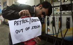 <p>A petrol kiosk worker puts up a sign beside a pump in the northern Indian city of Chandigarh January 8, 2009. Petrol stations ran dry and flights were delayed at India's busiest airport as a strike by state oil company officials demanding better pay entered a second day. REUTERS/Ajay Verma</p>
