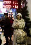 <p>Женщина на фоне вывески обменного пункта в Москве 30 декабря 2008 года. Центробанк РФ в воскресенье допустил первое в этом году ослабление рубля к бивалютной корзине, в результате чего доллар поднялся выше 30,5 рубля. REUTERS/Sergei Karpukhin</p>