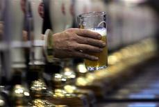<p>A glass of beer is handed between pumps at the Great British Beer Festival at Earls Court in London, August 1, 2006. REUTERS/Luke MacGregor</p>