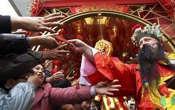 <p>El Dios de la Riqueza entrega 'lai see', o sobres rojos de la suerte, a compradores en Hong Kong, 26 ene 2009. Los chinos celebraron el lunes el Año Nuevo Lunar con la esperanza de que el Año del Buey sea mejor que un 2008 plagado de desastres. REUTERS/Garrige Ho (CHINA)</p>