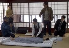 """<p>El director Yojiro Takita (segundo desde la derecha) guía a sus actores durante el rodaje de su filme """"Departures"""". Preparar los cadáveres para los ataúdes no es la profesión más glamorosa, pero una nominación al Oscar por """"Departures"""" ha lanzado una inesperada luz sobre el oculto mundo de los rituales mortuorios en Japón. REUTERS/@2008 Departures Film Partners/Handout</p>"""