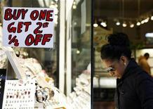 <p>A sign advertising sales is seen as a woman window shops outside a jewelry store in New York November 18, 2008. REUTERS/Shannon Stapleton</p>