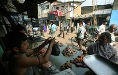<p>A woman buys meat at a roadside shop in Dharavi, considered Asia's biggest shantytown, in Mumbai, February 10, 2009. REUTERS/Punit Paranjpe</p>