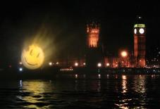 "<p>A logo to promote the film ""The Watchmen"" is projected onto fine spray water screen over the River Thames near to the Houses of Parliament in London, March 4, 2009. REUTERS/Luke MacGregor</p>"