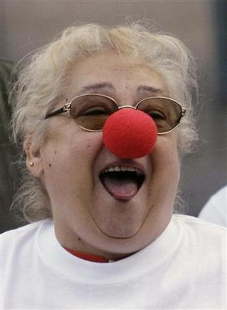 A woman attends a laughter therapy against the economic crisis in central Madrid October 1, 2008. REUTERS/Andrea Comas