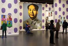 """<p>Visitors look at Mao paintings by U.S. artist Andy Warhol during the exhibition """"Le grand Monde d'Andy Warhol"""" (The World of Andy Warhol) at the Grand Palais museum in Paris March 17, 2009. REUTERS/Benoit Tessier</p>"""