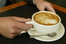 <p>Bryan Yeck, owner of Zeitgeist Kunst and Kafee in downtown Seattle, holds a latte at his cafe in downtown Seattle on September 11, 2003. EUTERS/Anthony P. Bolante</p>