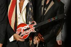 """<p>Aerosmith's Joe Perry (L) holds a guitar-shaped video game controller during a press conference for the new video game """"Guitar Hero: Aerosmith"""" in New York, June 27, 2008. REUTERS/Lucas Jackson</p>"""