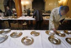 <p>A man views silverware at the Savoy Hotel in central London, December 17, 2007. REUTERS/Toby Melville</p>