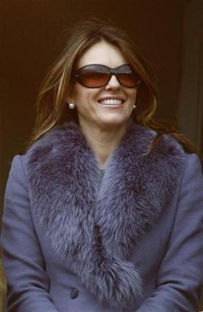 Britain's Liz Hurley smiles on the first day of the Cheltenham Festival horse racing meeting in Gloucestershire, western England March 10, 2009. REUTERS/ Eddie Keogh