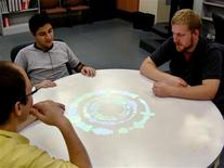 """<p>People are shown using the """"Conversation Clock"""" at the University of Illinois in this undated publicity photo released to Reuters on March 23, 2009. Each colored ring shows whether one person is dominating the conversation of whether they are taking turns. Their voice appears on a computer terminal as vibrant colors -- red, yellow, blue, green -- the image growing in size if the voice gets louder, overlapping another color as it interrupts or abruptly narrowing with silence. REUTERS/Tony Bergstrom/University of Illinois/Handout</p>"""