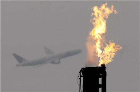 An airplane flies near a gas flare from a factory at Keihin industrial zone in Kawasaki, south of Tokyo November 12, 2008. REUTERS/Toru Hanai