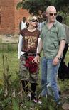 <p>La cantante Madonna parada al lado de su guardaespaldas en la escuela que ella financia, en Lilongwe, Malaui, 30 mar 2009. El Gobierno de Malaui respalda el intento de la cantante estadounidense Madonna de adoptar un segundo niño en el país africano, dijo la ministra de Información el jueves, una posición que probablemente molestará a grupos de derechos civiles que se oponen a esa adopción. REUTERS/Antony Njuguna</p>