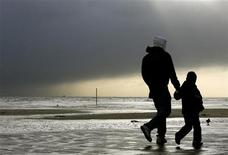 <p>People walk on the beach after a tidal surge in Great Yarmouth, England, November 9, 2007. REUTERS/Darren Staples</p>