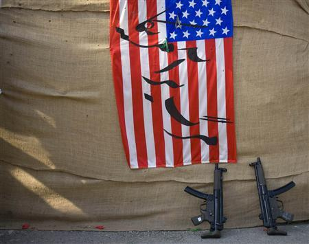 Two rifles are seen next to the U.S. flag with a Persian script which reads, ''Down with USA'', at a war exhibition held by the Iranian army to mark the anniversary of army day at a military base in central Tehran April 14, 2009. REUTERS/Morteza Nikoubazl