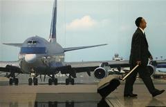 <p>A traveller walks past a photograph of a Cathay Pacific 747 passenger jet, at the Hong Kong International Airport, April 16, 2009. REUTERS/Bobby Yip</p>