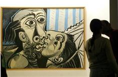 <p>A couple kiss themselves next to Pablo Picasso's 'Le Baiser' 1969 oil painting at The Oca pavilion in Ibirapuera Park, Sao Paulo, February 1, 2004. T REUTERS/Paulo Whitaker</p>