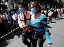 <p>Una mujer recibe ayuda de un socorrista durante la evacuación de edificios tra un sismo en Ciudad de México, 27 abr 2009. Un sismo de magnitud 5.6 sacudió el lunes a una amplia zona del centro y costa Pacífico de México, causando daños leves y preocupación en una población ya alarmada por la mortal epidemia de influenza porcina que se extiende por el país. REUTERS/Henry Romero</p>