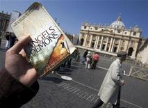 """<p>A guide with the """"Official Angels & Demons Tour"""" holds a copy of the book by Dan Brown while accompanying a group of American tourists retracing its plot at Saint Peter's square in the Vatican, May 1, 2009. REUTERS/Chris Helgren</p>"""