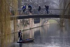 <p>Cyclists cross a bridge as a man punts on the River Cam in Cambridge, central England February 20, 2008. REUTERS/Darren Staples</p>