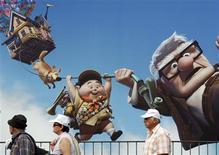 """<p>Pessoas passando próximo a um gigante cartaz da animação """"Up"""" em Cannes. 12/05/2009. REUTERS/Regis Duvignau</p>"""
