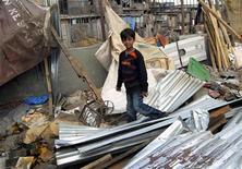 """<p>Azharuddin Ismail de """"Slumdog Millionaire"""" camina entre los restos de lo que fue su hogar, en Mumbai, 14 mayo 2009. Las autoridades de la ciudad de Mumbai demolieron el jueves la precaria vivienda de la estrella infantil de """"Slumdog Millionaire"""", forzando a su familia a vivir en las calles apenas unos meses después de que la película ganadora del Oscar lo lanzara a la fama mundial. REUTERS/Stringer</p>"""