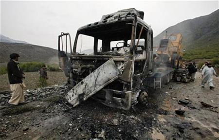 A truck carrying construction equipment smoulders after being set on fire by insurgents in the Kunar Valley in eastern Afghanistan in this January 3, 2009 file photo. REUTERS/Bob Strong