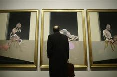 """<p>A man stands next to the painting """"Triptych"""" by Irish-born artist Francis Bacon during the media presentation of a Francis Bacon retrospective exhibit in Madrid January 30, 2009. REUTERS/Susana Vera</p>"""