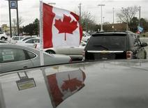<p>A Canadian flag flies from the window of a General Motors vehicle at a car dealership in Toronto December 12, 2008. REUTERS/Mike Cassese</p>