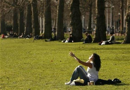 A woman sits in the sunshine in St James Park, central London February 21, 2009. REUTERS/Luke MacGregor
