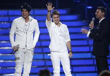 """<p>Finalists Adam Lambert (L) and Kris Allen appear on stage with host Ryan Seacrest (R) during the finale of Season 8 of """"American Idol"""" in Los Angeles May 20, 2009. REUTERS/Danny Moloshok</p>"""