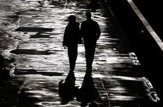 <p>A couple walk along the bank of the River Thames after a heavy downpour of rain in London April 28, 2009. REUTERS/Luke MacGregor</p>