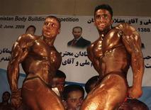 <p>Hombres afganos posan durante la competencia nacional de fisiculturismo en un teatro en Kabul, 2 jun 2009. A la izquierda, Shukrullah Shakili, ganador de Mr. Afganistán 2009. Dentro de una pequeña, oscura y húmeda sala de cine en el corazón de la capital afgana, una audiencia repleta de hombres grita y chifla mientras musculosas figuras bronceadas flexionan sus bíceps con la esperanza de ser coronadas Mr. Afganistán. REUTERS/Omar Sobhani</p>