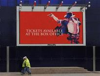 <p>Workmen pass an advertising board for the forthcoming Michael Jackson concerts at the O2 Arena in London March 13, 2009. REUTERS/Toby Melville</p>