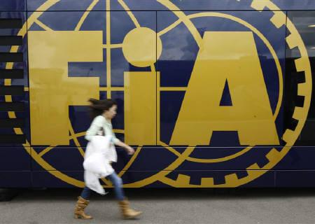 A woman walks past the International Automobile Federation (FIA) bus in the paddock ahead of Sunday's F1 British Grand Prix at Silverstone in England June 18, 2009. Formula One plunged into its biggest crisis in 60 years on Friday with eight of the 10 teams announcing plans to set up their own championship. REUTERS/Andrew Winning
