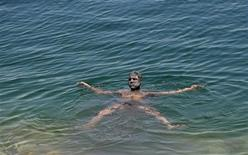 <p>Un uomo nuota nel Mar Morto. REUTERS/Ammar Awad</p>