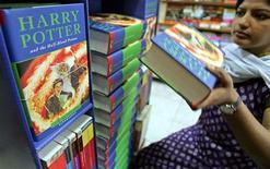 """<p>Служащая в книжном магазине показывает книгу """"Гарри Поттер и принц-полукровка"""" в Нью-Дели 16 июля 2005 года. Гарри Поттер возвращается на экраны кинотеатров планеты, обещая вновь принести неплохую прибыль создателям шестой части приключений юного мага - компании Warner Brosers. REUTERS/Adnan Abidi</p>"""